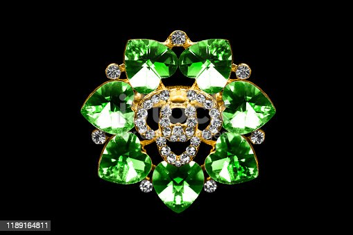 Gold brooch with emeralds and diamonds on black background