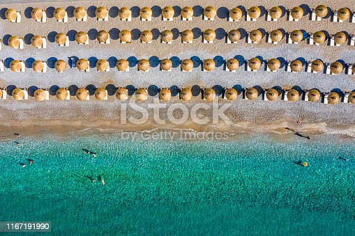 Beach coastline taken from a drone, with rows of beach umbrellas and sunbeds.
