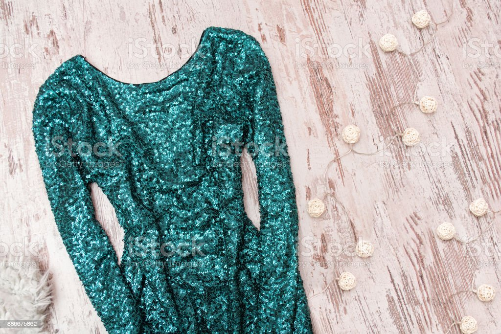Emerald dress in sequins and garland on a wooden background. Fashionable concept. stock photo