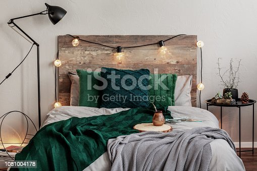 Emerald green and grey bedding on double bed with wooden headboard