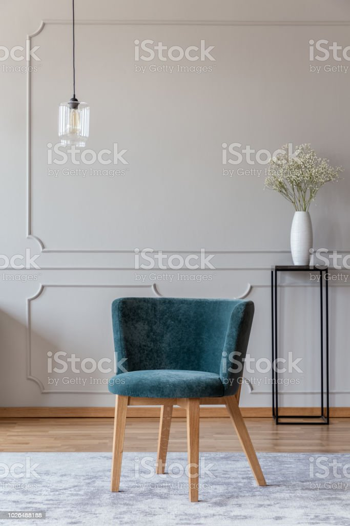 Picture of: Emerald Green Chair With Wooden Legs On A Gray Rug In A Stylish Living Room Interior With Molding On Beige Walls Stock Photo Download Image Now Istock