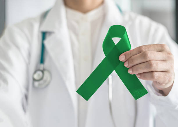 Emerald green or jade color ribbon in doctor's hand symbolic for Liver Cancer and Hepatitis B disease awareness concept stock photo