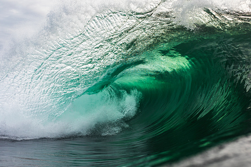 A powerful emerald green wave breaking in the ocean against a stormy backdrop, photographed in the morning out in the ocean.