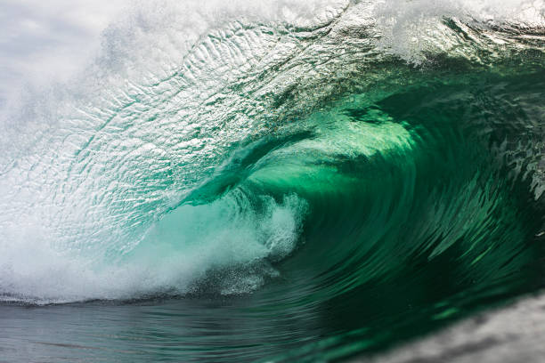 Emerald green wave breaking in the ocean stock photo
