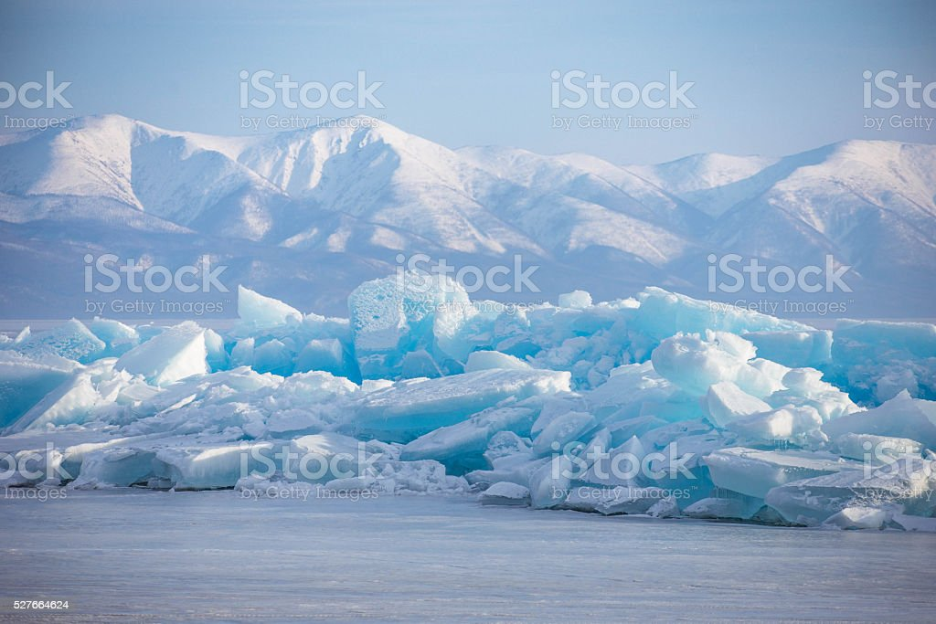 Emerald ice floe on background of mountains stock photo