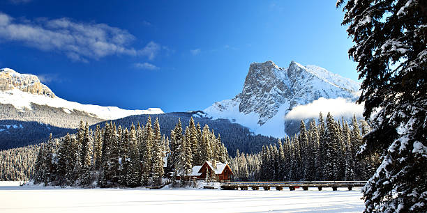 Emerald Lake Lodge Winter Island A view of the Emerald Lake Lodge, situated in the Canadian Rocky Mountains, in winter. A long bridge leads to the lodge over the frozen lake surface. emerald lake stock pictures, royalty-free photos & images