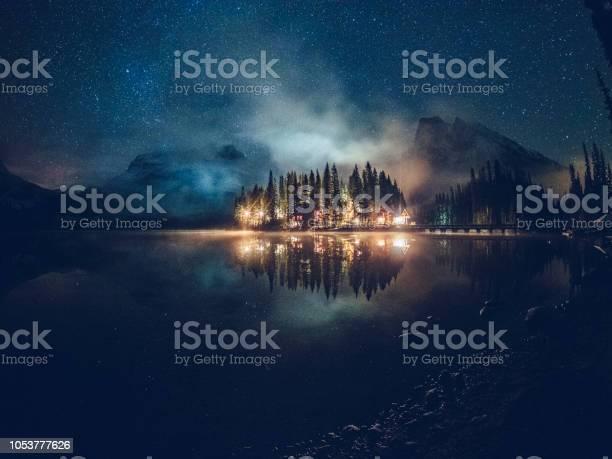 Photo of Emerald lake with illuminated cottage under milky way