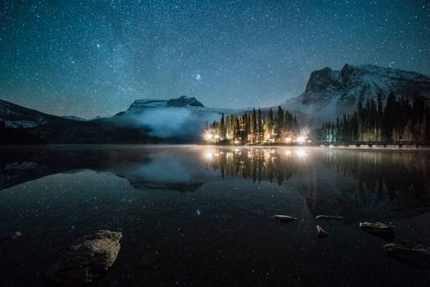 Emerald lake with illuminated cottage under milky way Emerald lake with illuminated cottage under milky way,and Mount Burgess on background,in Yoho national park,British Columbia, Canada. emerald lake stock pictures, royalty-free photos & images