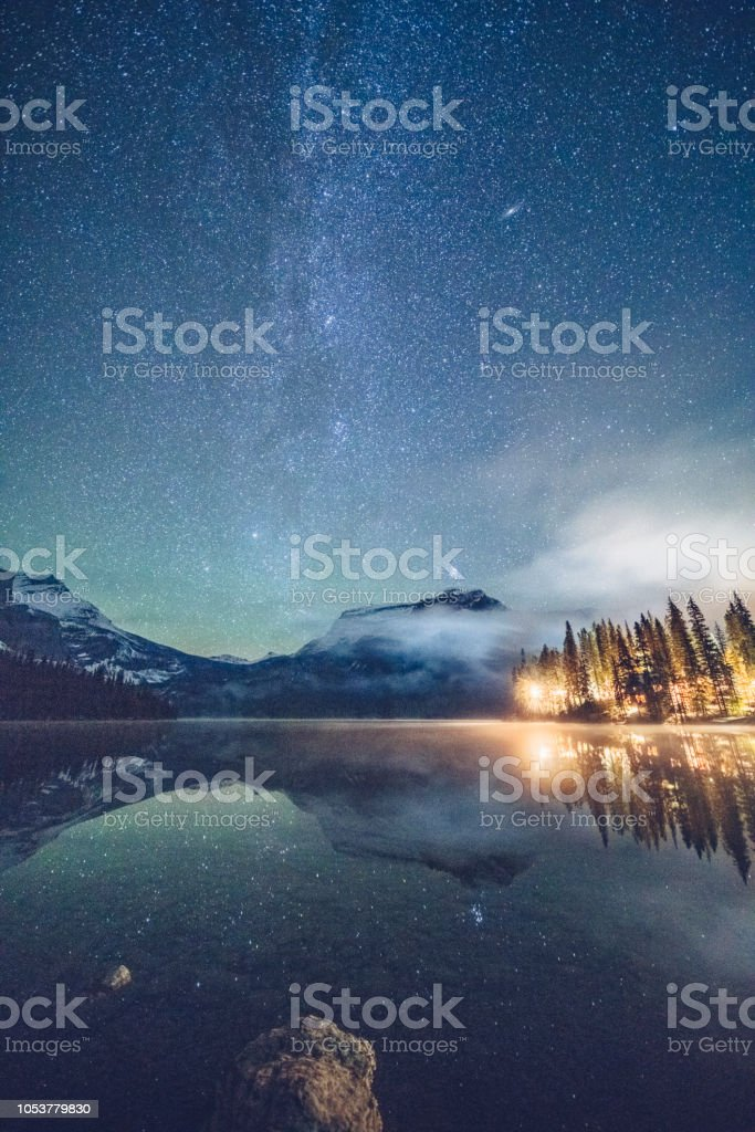 Emerald lake with illuminated cottage under milky way Emerald lake with illuminated cottage under milky way,and Mount Burgess on background,in Yoho national park,British Columbia, Canada. Astronomy Stock Photo