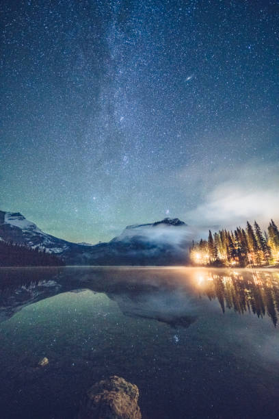 Emerald lake with illuminated cottage under milky way stock photo