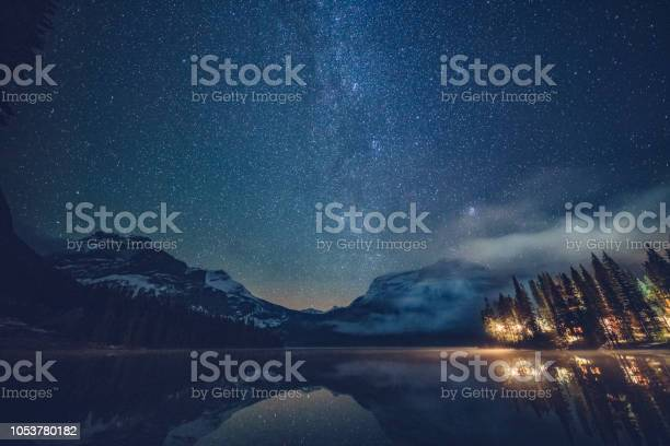 Emerald Lake With Illuminated Cottage Under Milky Way Stock Photo - Download Image Now