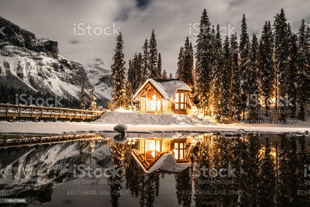 Emerald lake with lodge in Yoho national park, British Columbia, Canada; shot at night with lights on in the chalet reflection on lake 12/19/2018: Emerald lake in Yoho national park, British Columbia, Canada. Shot in winter with deep snow covering lakeshore and pine trees, wood lodge in the photo. Awe Stock Photo