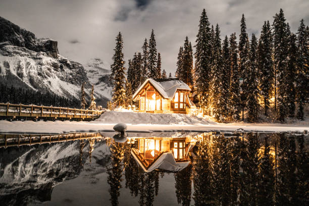 Emerald lake with lodge in Yoho national park, British Columbia, Canada; shot at night with lights on in the chalet reflection on lake 12/19/2018: Emerald lake in Yoho national park, British Columbia, Canada. Shot in winter with deep snow covering lakeshore and pine trees, wood lodge in the photo. emerald lake stock pictures, royalty-free photos & images