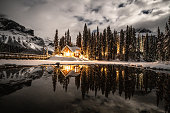 12/19/2018: Emerald lake in Yoho national park, British Columbia, Canada. Shot in winter with deep snow covering lakeshore and pine trees, wood lodge in the photo.
