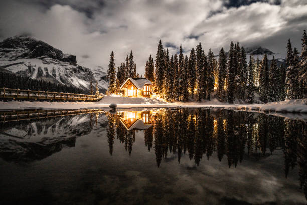Emerald lake with lodge in Yoho national park, British Columbia, Canada; shot at night with lights on in the chalet reflection on lake stock photo