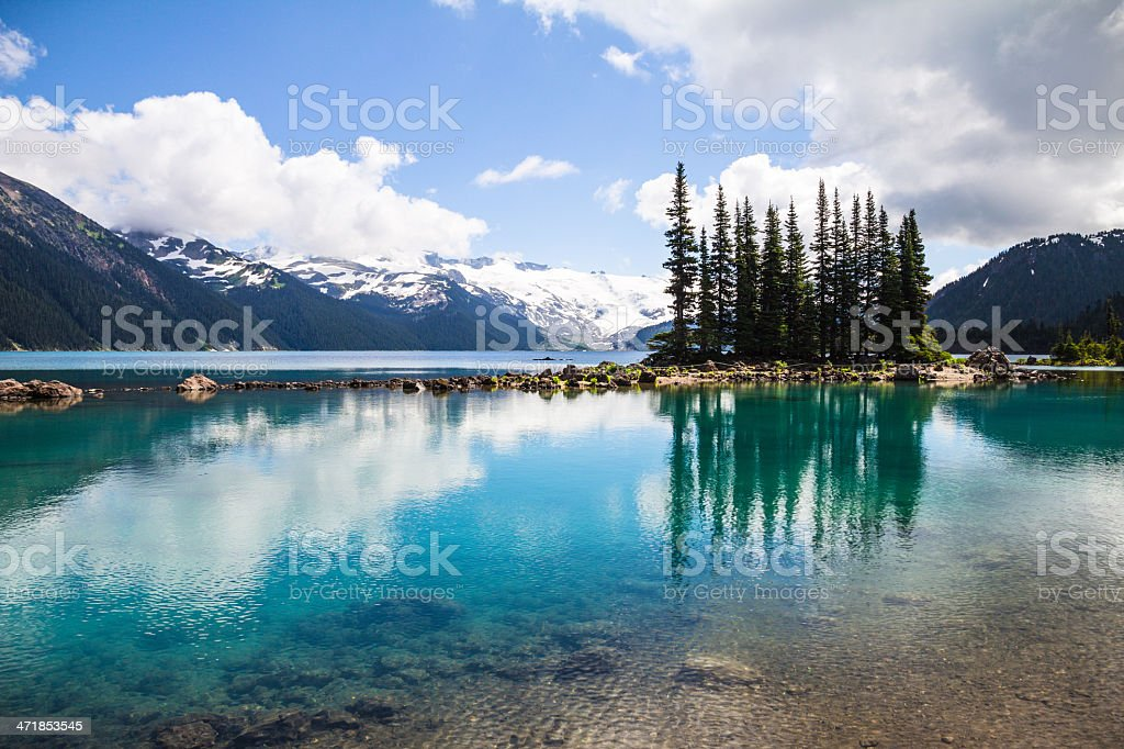Emerald waters of Garibaldi Lake reflect bottle-green tree silhouettes stock photo