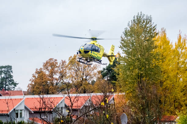 Emergency ambulance rescue helicopter landing in bad weather in a residential area with buildings and trees. stock photo