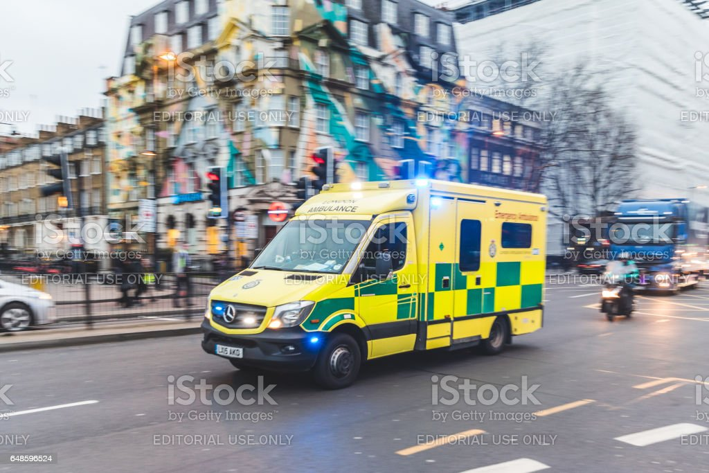Emergency ambulance rushing on the street in London stock photo