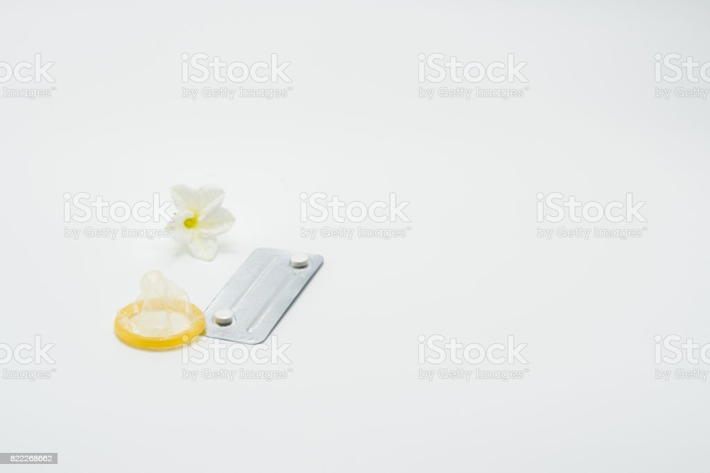 Emergency contraceptive pills, condom and flower on white background - Stock image .