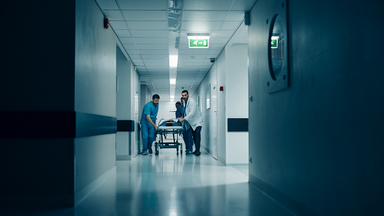 istock Emergency Department: Doctors, Nurses and Surgeons Push Gurney / Stretcher with Seriously Injured Patient towards the Operating Room. Light Dramatically Turns on. 1043634456