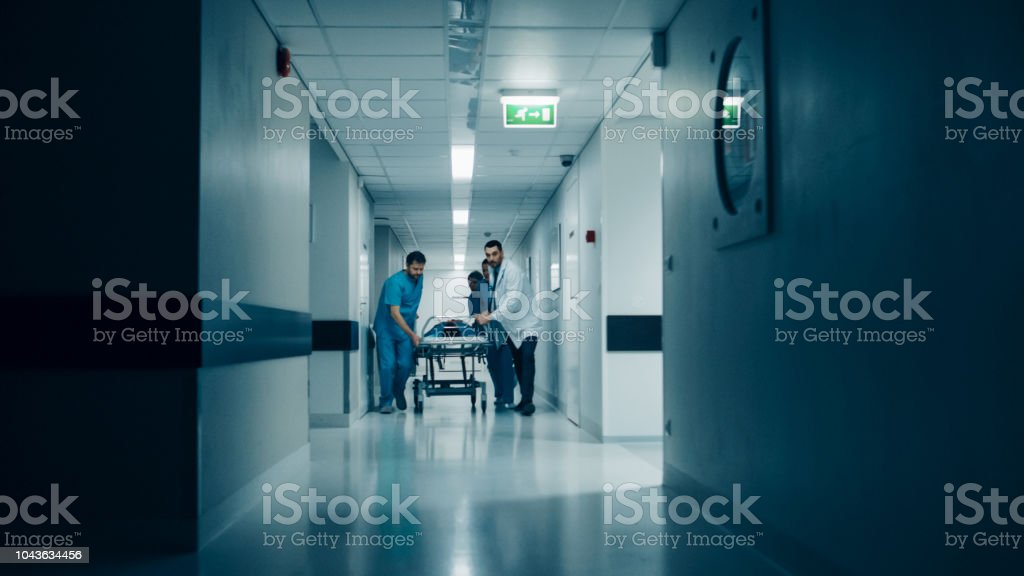 Emergency Department: Doctors, Nurses and Surgeons Push Gurney / Stretcher with Seriously Injured Patient towards the Operating Room. Light Dramatically Turns on. stock photo