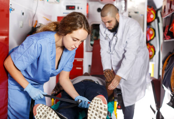 Emergency doctors fixing  patient on stretcher Emergency doctors fixing  patient on stretcher in ambulance car acute angle stock pictures, royalty-free photos & images
