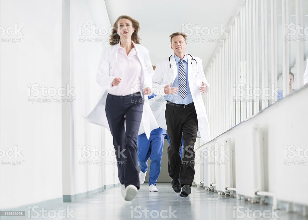 Three doctors running in a hospital corridor.