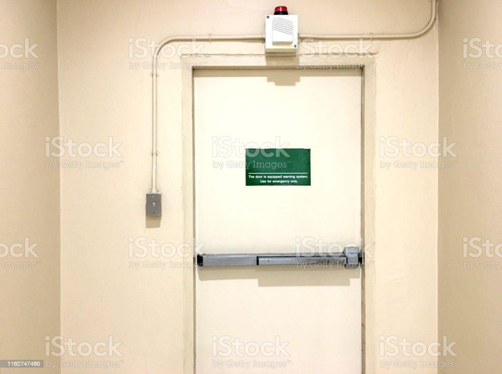 Emergency exit door with siren alarm in store building.