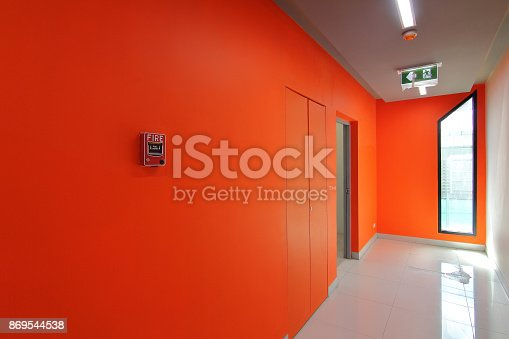 istock Emergency exit of the building with fire exit sign and fire alarm 869544538