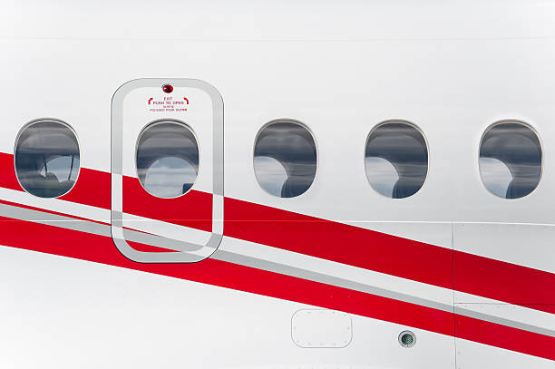 Emergency exit on red and white airplane stock photo