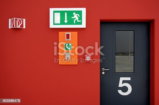 istock Emergency exit sign and fire alarm button and black door 503386478