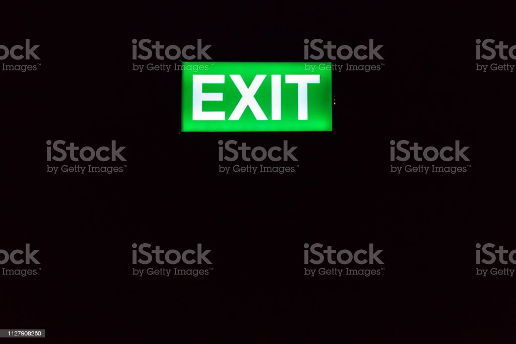 Emergency exit sign glowing in the dark. Illuminated green exit sign....