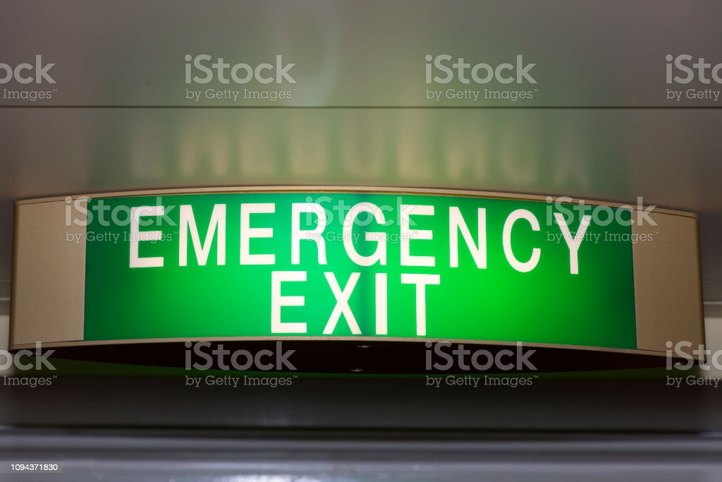 Emergency exit sign lit in a hotel corridor