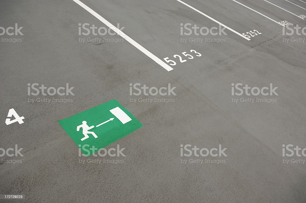 Emergency exit sign painted on the ground of a parking lot