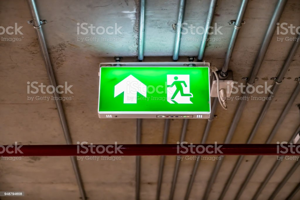 Green Emergency exit sign with metal pipes