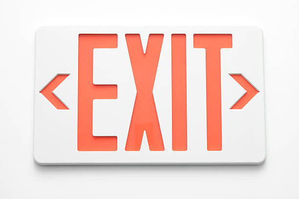 emergency exit signs on white wall - exit sign stock photos and pictures