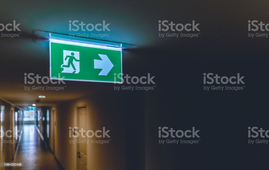 Emergency fire exit green sign at the corridor in office building.,...