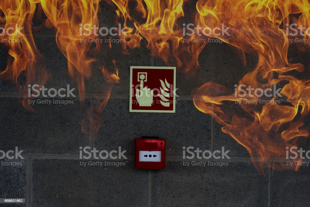 Emergency Fire Exit on the stone wall with fire flames stock photo