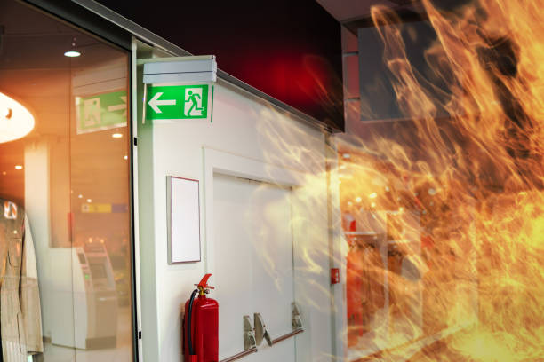 Emergency fire exit sign and fire in shopping mall. stock photo