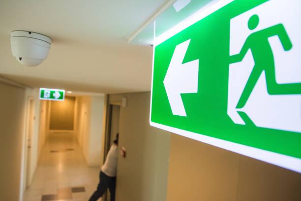 fire exit rettungszeichen auf dem flur im gebäude - kinderlandverschickung stock-fotos und bilder