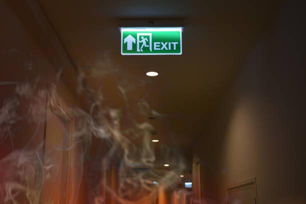 notfall feuer ausgangsschild zeigen den weg, mit dem rauch feuer brennen zu entkommen. - kinderlandverschickung stock-fotos und bilder