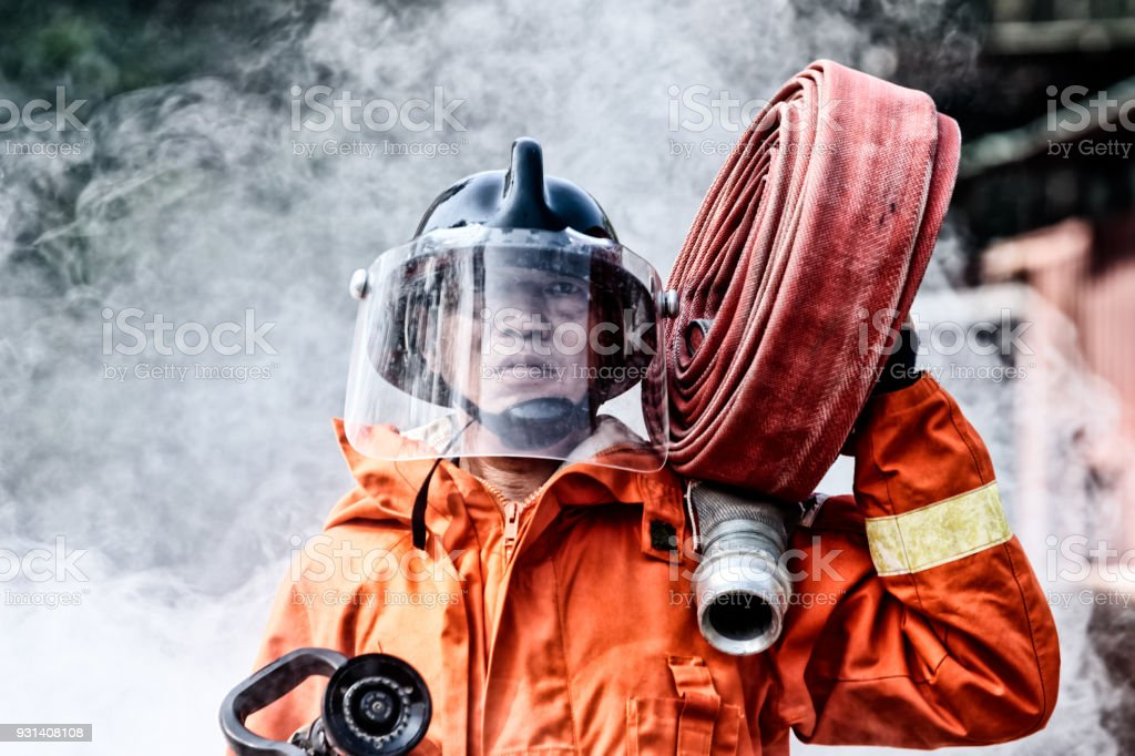 Emergency Fire Rescue training, firefighters in uniform,  carry a water hose run through flame stock photo
