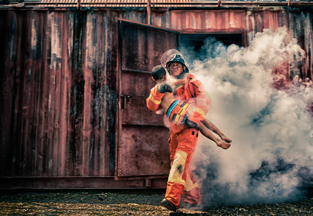 Emergency Fire Rescue training,Firefighters save the boy from burnt place stock photo