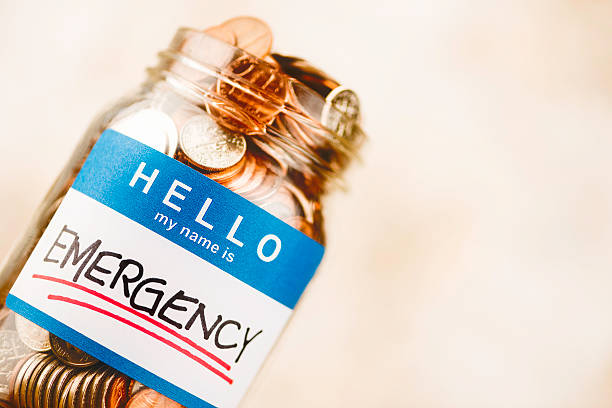 Emergency fund money jar filled with American currency Emergency fund money jar filled with American currency emergency sign stock pictures, royalty-free photos & images