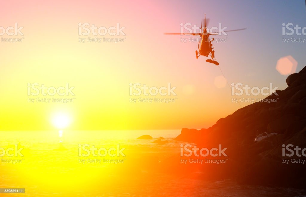 Emergency helicopter lowers a stretcher to car crash victim stock photo