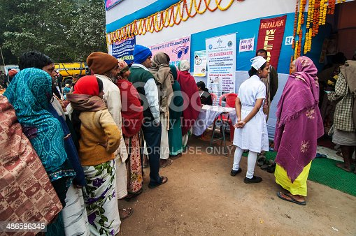Kolkata, India - January 12, 2014: Hindu devotees queing up for medicine at emergency medical camp at Babughat transit Camp, Kolkata. Every year Hindu devotees from all over the country visits Gangasar and stays for some days in Babughat transit camp, Kolkata.