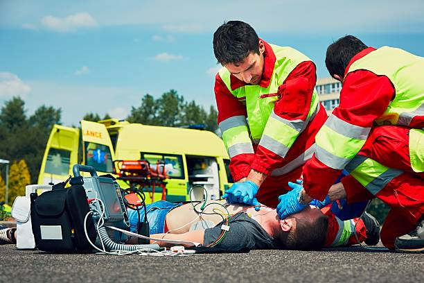 Emergency medical service Cardiopulmonary resuscitation. Rescue team (doctor and a paramedic) resuscitating the man on the street. ambulance staff stock pictures, royalty-free photos & images
