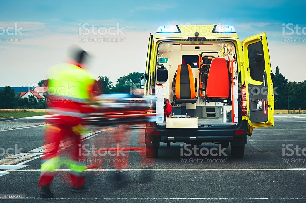 Emergency medical service Emergency medical service. Paramedic is pulling stretcher with patient to the ambulance car. Accidents and Disasters Stock Photo