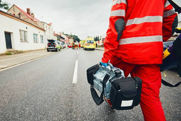 Emergency medical service Hand of the doctor with defibrillator. Teams of the Emergency medical service are responding to an traffic accident. ambulance staff stock pictures, royalty-free photos & images