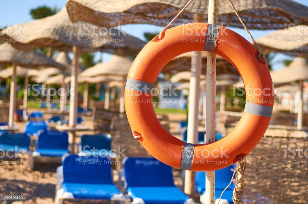 Emergency orange life buoy on sea beach stock photo